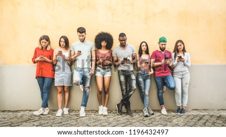 Multiracial friends using smartphone against wall at university college backyard - Young people addicted by mobile smart phone - Technology concept with always connected millennials - Filter image #1196432497