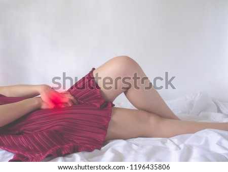 The woman has itching on his genitals.Asian women wear red clothes on their bed, they have itching in the vagina.Girl hands placed at the vagina. #1196435806