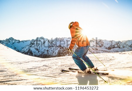 Professional skier athlete skiing at sunset on top of french alps ski resort - Winter vacation and sport concept with adventure guy on mountain top riding down the slope - Warm bright sunshine filter #1196453272