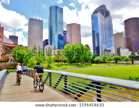 Bicyclists cross wooden bridge in Buffalo Bayou Park, with a beautiful view of downtown Houston (skyline / skyscrapers) in background on a summer day - Houston, Texas, USA  Royalty-Free Stock Photo #1196454610