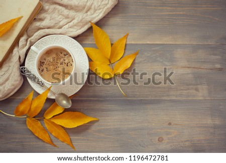 Cup of coffee with milk in sunny autumn day. Warm wool clothes and yellow leaves beside the cup. Flat lay. Copy space #1196472781