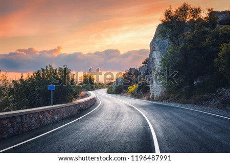 Mountain road at sunset. Landscape with rocks, orange sunny sky with clouds and beautiful asphalt road in the evening in summer. Vintage toning. Travel background. Scenery with highway. Transportation #1196487991