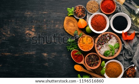 A set of spices and herbs. Indian cuisine. Pepper, salt, paprika, basil, turmeric. On a black wooden chalkboard. Top view. Free copy space. #1196516860