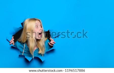 Through paper. Advertising. Copy space. Black friday. Surprised girl looking through hole in paper. Emotions. Season sales. Discount. Sale. Copyspace. Surprised girl making hole in paper. #1196517886