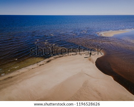 Aerial view of Engure beach in Latvia. River meets Baltic sea. Lonely man on the shore. Nice sunny day. #1196528626