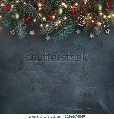 Christmas background with fir twigs, red berries, cones and Xmas lights on dark abstract background with plenty of text space #1196574049