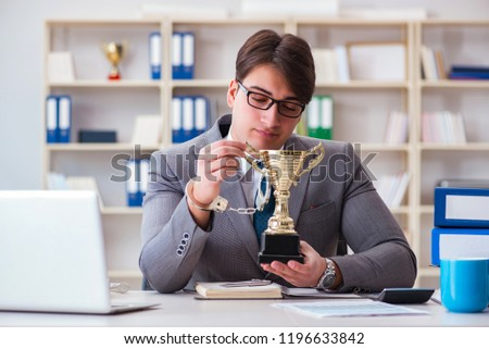 Businessman with golden cup in the office #1196633842