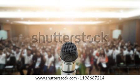 Microphone over the Abstract blurred photo of conference hall or seminar room with attendee background,Small Business training concept,Public speaking Royalty-Free Stock Photo #1196667214