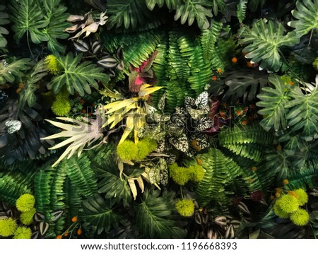 Seamless pattern with artificial tropical leaves and flowers on dark background. Tropic rain forest foliage texture. #1196668393