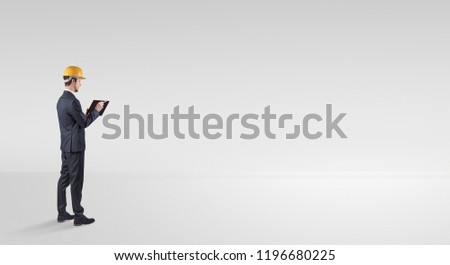 Young architect with construction helmet standing in an empty space and holding a plan #1196680225