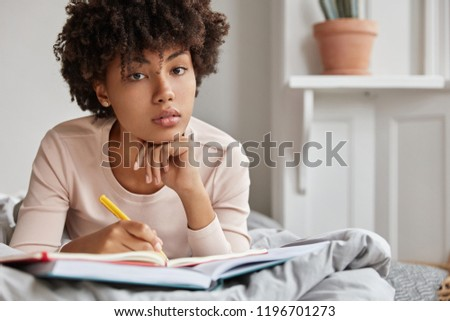 Close up shot of serious dark skinned female college student does home assigment in bed, prepares school test, writes in notebook with pen, keeps hand under chin, enjoys cozy domestic atmosphere #1196701273