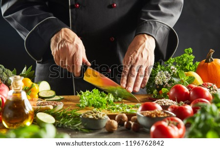 Restaurant worker cutting up green leafy herbs on cutting board next to tomatoes and cucumber slices #1196762842