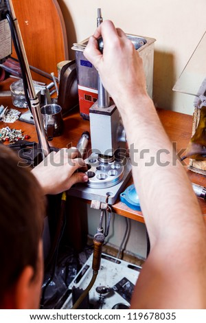 Jeweler changing ring size with the help of resizer tool