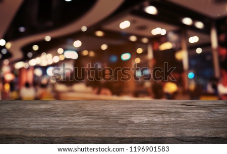 Empty dark wooden table in front of abstract blurred bokeh background of restaurant . can be used for display or montage your products.Mock up for space #1196901583