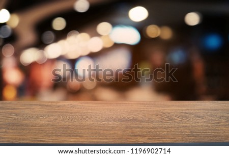 Empty dark wooden table in front of abstract blurred bokeh background of restaurant . can be used for display or montage your products.Mock up for space #1196902714
