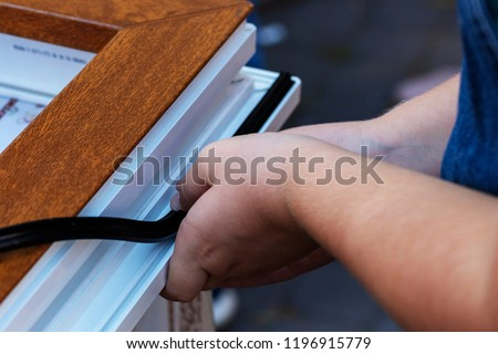 Professional sealing a window frame. Rubber insulation  in a plastic window. Concept improvement of sealing, sound insulation, thermal insulation of windows and doors. Hands applying rubber strip. #1196915779