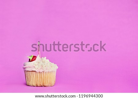 Pretty strawberry or cherry flavored frosted cupcake decorated with white chocolate shavings and one candle burning. Free space for copy text.