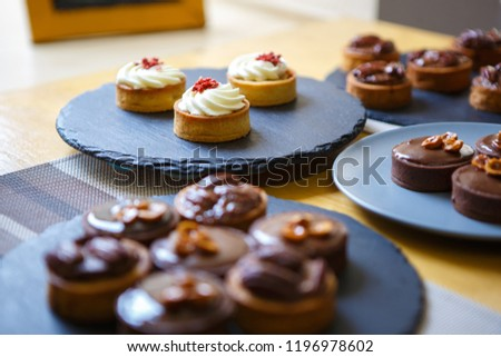 Delicious cupcakes served on black slate ceramic plate in restaurant. Tasty fresh baked pastry products in cafe for lunch #1196978602