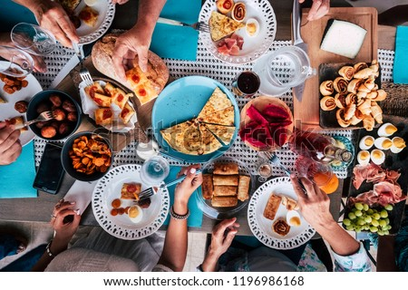 Above aerial view of group of friends having fun eating together at lunch or dinner with a table full of different and colorful food and technology mobile phone. mix of hands of caucasian people  #1196986168