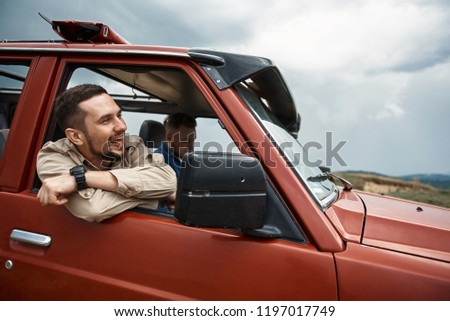 Cheerful handsome young man sitting in the off-road car while travelling with his friend #1197017749