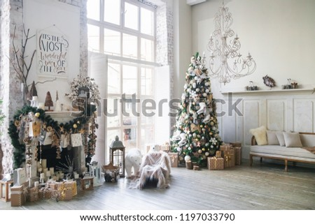 Christmas morning interior with christmas tree decorated fireplace and big window. White loft. Vintage chandelier. Beige sofa. White and gold balls on the Christmas tree. Polar bear. New Year.