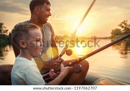 Happy Father and Son together fishing from a boat at sunset time in summer day under beautiful sky on the lake. Royalty-Free Stock Photo #1197062707
