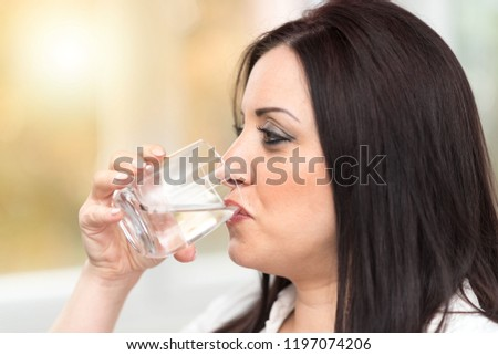 Portrait of young attractive woman drinking water #1197074206