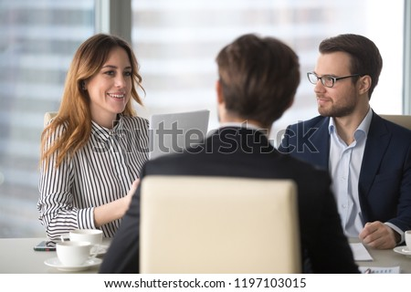 Young broker businesswoman talking to business partners. Woman consulting, giving instructions, explaining terms of contract. Man in glasses looking colleague and listening. Royalty-Free Stock Photo #1197103015