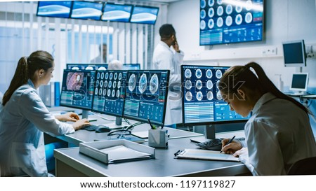 Team of Professional Scientists Work in the Brain Research Laboratory. Neurologists / Neuroscientists Surrounded by Monitors Showing CT, MRI Scans Having Discussions and Working on Personal Computers. Royalty-Free Stock Photo #1197119827