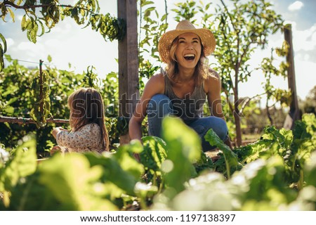 Beautiful young female farmer working in her garden with her daughter sitting by. Young mother and daughter working in the farm. #1197138397