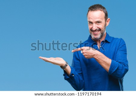 Middle age hoary senior man over isolated background amazed and smiling to the camera while presenting with hand and pointing with finger. #1197170194