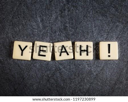 Letter tiles on black slate background spelling Yeah! #1197230899