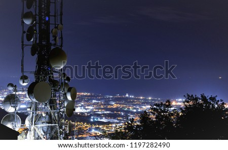 Telecommunications tower, antenna and satellite dish and city at night as background Royalty-Free Stock Photo #1197282490