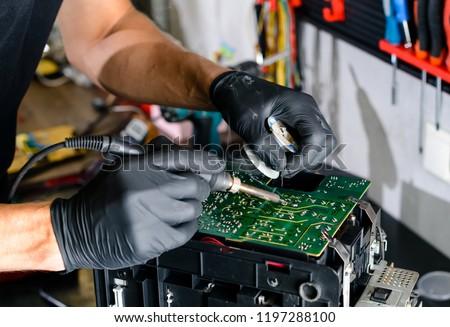 man solder a chip in a workshop close-up #1197288100