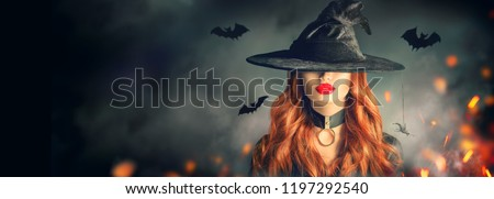 Halloween Witch girl portrait. Beautiful young woman in witches hat with long curly red hair and bright lips. Over spooky dark magic forest background. Wide Halloween party art design #1197292540