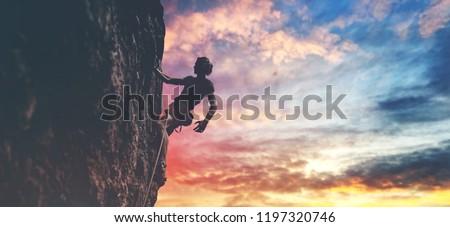 man rock climber with long hair. side view of young man rock climber in bright red shorts resting while climbing the challenging route on the cliff on the colorful down sky background. rock climber #1197320746
