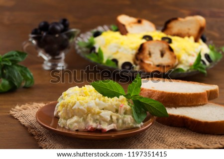 A portion of a cold snack on a plate with basil  leaves, toast, pickled olives. #1197351415