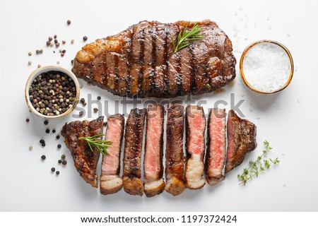 Two grilled marbled beef steaks striploin with spices isolated on white background, top view #1197372424