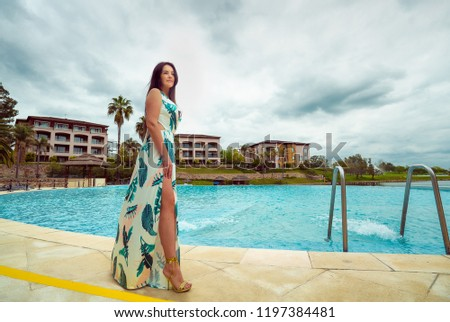 Woman in dress standing near the pool #1197384481