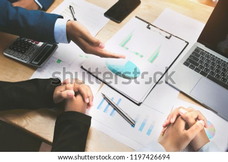 teamwork meeting discussing a new project and hand pointing graph on paperwork #1197426694