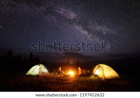 Camping in mountains at night. Bright bonfire burning between two hikers, boy and girl sitting opposite each other near illuminated tents under beautiful evening starry sky and Milky way #1197452632
