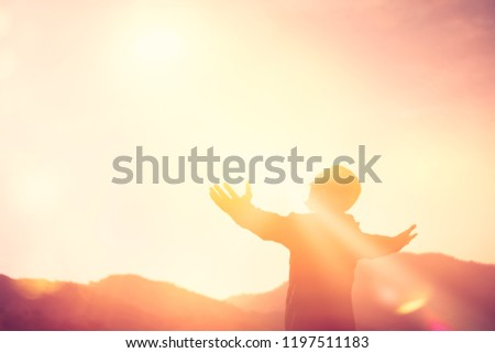 Copy space of man rise hand up on top of mountain and sunset sky abstract background. Freedom and travel adventure concept. Vintage tone filter effect color style. #1197511183