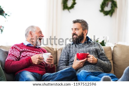 A senior father and adult son sitting on a sofa at home at Christmas time, talking. #1197512596