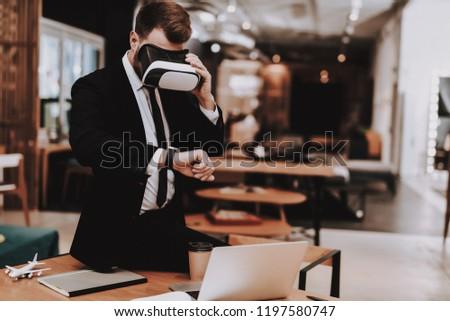 Virtual Reality. Wrist Watch. Business Suit. Laptop. Sit. Brainstorm. Young Guy. Businessman. Work in Office. Creative Worker. Create Ideas. Businesspeople. Workplace. Inspiration. Comfortable Office. #1197580747