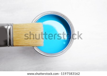 Can with blue paint and brush on light background, top view #1197583162