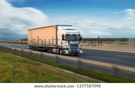 Truck with container on highway, cargo transportation concept. Shaving effect. #1197587098