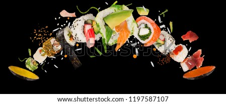 Pieces of delicious japanese sushi frozen in the air. Isolated on black background #1197587107