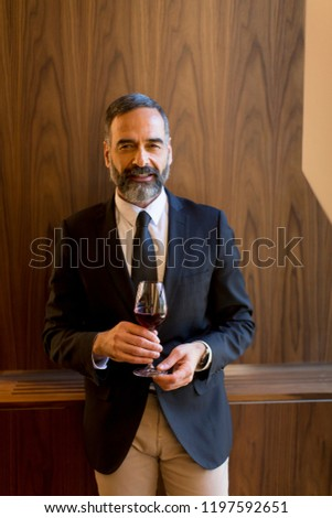 Portrait of handsome man with glass of red wine #1197592651