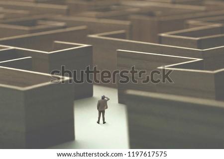 man lost in a complex maze, surreal concept #1197617575