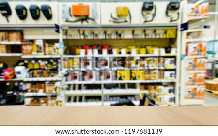 Mockup. Welding equipment. Shop with a variety of electrical equipment for welding. Defocused, blurred image. In the foreground is the top of a wooden table, counter. #1197681139